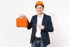 Lächelnder Geschäftsmann im dunklen Anzug, schützender Hardhatholdingfall mit Instrumenten oder Werkzeugkasten und Zeigen des Zei lizenzfreies stockbild