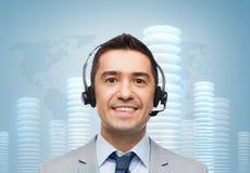 Lächelnder Geschäftsmann im Kopfhörer über Stückchenmünze Stockbild