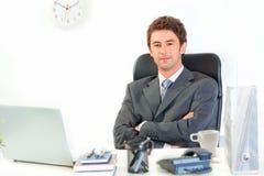 Lächelnder Geschäftsmann mit den gekreuzten Armen auf Kasten Lizenzfreies Stockfoto