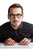 Lächelnder Geschäftsmann mit Gläsern schreibend auf Tastatur Stockbild