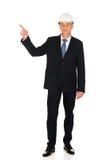 Lächelnder Geschäftsmann mit Schutzhelm oben zeigend Stockfoto