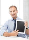 Lächelnder Geschäftsmann mit Tabletten-PC im Büro lizenzfreie stockfotografie
