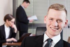 Lächelnder Geschäftsmann und seine Mitarbeiter Stockfoto