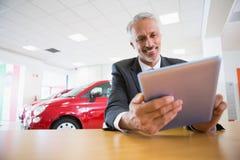Lächelnder Geschäftsmann unter Verwendung der Tablette an seinem Schreibtisch Stockbild