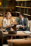 Lächelnder Geschäftsmann unter Verwendung des Laptop cmputer am Schreibtisch und Unterhaltung mit einer Frau stockfotos