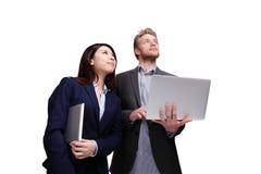 Lächelnder Geschäftsmann unter Verwendung des Laptop cmputer am Schreibtisch und Unterhaltung mit einer Frau Stockfoto