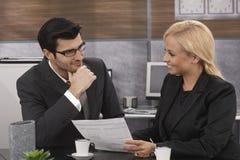 Lächelnder Geschäftsmann unter Verwendung des Laptop cmputer am Schreibtisch und Unterhaltung mit einer Frau Stockbild