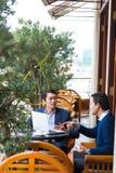 Lächelnder Geschäftsmann unter Verwendung des Laptop cmputer am Schreibtisch und Unterhaltung mit einer Frau Lizenzfreie Stockfotos