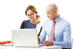 Lächelnder Geschäftsmann unter Verwendung des Laptop cmputer am Schreibtisch und Unterhaltung mit einer Frau Stockfotografie