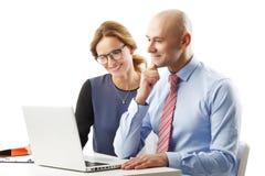Lächelnder Geschäftsmann unter Verwendung des Laptop cmputer am Schreibtisch und Unterhaltung mit einer Frau Lizenzfreies Stockbild