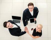 Lächelnder Geschäftsmann unter Verwendung des Laptop cmputer am Schreibtisch und Unterhaltung mit einer Frau Draufsicht von drei  Stockbilder