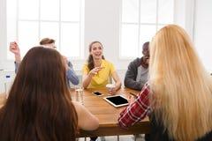 Lächelnder Geschäftsmann unter Verwendung des Laptop cmputer am Schreibtisch und Unterhaltung mit einer Frau Junges Team im moder stockfotos