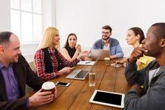 Lächelnder Geschäftsmann unter Verwendung des Laptop cmputer am Schreibtisch und Unterhaltung mit einer Frau Junges Team im moder lizenzfreie stockbilder
