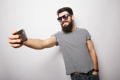 Lächelnder glücklicher Hippie-Mann in den Sonnenbrillen mit dem Bart, der selfie mit Handy nimmt Stockbild