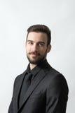 Lächelnder glücklicher junger bärtiger eleganter Mann im schwarzen Anzug Stockfotografie