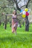 Lächelnder glücklicher kaukasischer blonder weiblicher Betrieb im Wald Lizenzfreies Stockbild