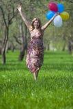 Lächelnder glücklicher kaukasischer blonder weiblicher Betrieb im Wald Lizenzfreie Stockbilder