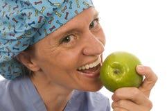 Lächelnder glücklicher Krankenschwesterdoktor, der grünen Apfel isst Lizenzfreies Stockfoto