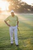 Lächelnder Golfspieler mit der Hand auf Hüfte beim Halten des Golfclubs Stockfoto