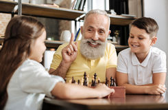 Lächelnder Großvater, der Idee über folgenden Schachzug hat Stockbilder