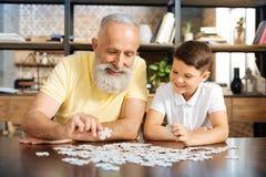 Lächelnder Großvater und Enkel, die zusammen ein Puzzlen tun stockfoto