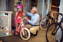 Lächelnder Großvater und Mädchen, die Fahrrad und Sturzhelme im Fahrradgeschäft wählen lizenzfreie stockfotos