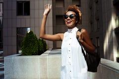 Lächelnder Gruß des jungen schönen afrikanischen Mädchens, der hinunter Stadt geht Lizenzfreie Stockfotografie