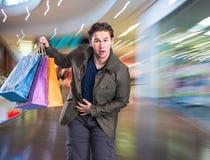 Lächelnder gutaussehender Mann mit Einkaufstaschen Stockbild