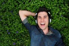 Lächelnder gutaussehender Mann mit Kopfhörern draußen lizenzfreies stockbild