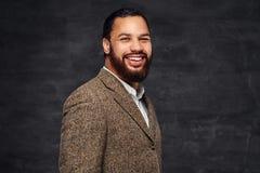 Lächelnder hübscher bärtiger afro-amerikanischer Geschäftsmann in einer braunen klassischen Jacke stockfotos