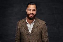 Lächelnder hübscher bärtiger afro-amerikanischer Geschäftsmann in einer braunen klassischen Jacke lizenzfreie stockbilder