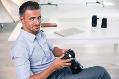Lächelnder hübscher Fotograf, der Kamera verwendet Lizenzfreie Stockbilder
