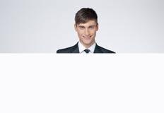 Lächelnder hübscher Geschäftsmann hinter weißem Plakat. Stockbilder