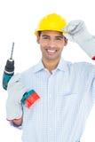 Lächelnder hübscher junger Heimwerker, in stark gehabt mit Bohrgerät lizenzfreies stockbild