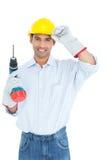 Lächelnder hübscher junger Heimwerker, in stark gehabt mit Bohrgerät stockfotos