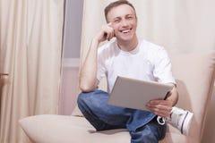 Lächelnder hübscher kaukasischer Mann mit Tablet-Computer auf Couch Stockbilder