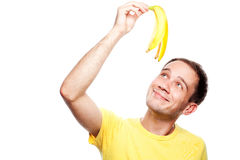Lächelnder hübscher Kerl, der Bananenschale hält Stockfoto