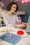 Lächelnder hübscher Mädchen Blogger, der auf Laptop schreibt Stockbilder