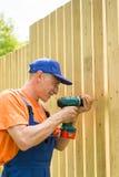 Lächelnder Heimwerker wirbelt eine Schraube Lizenzfreies Stockbild