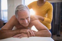 Lächelnder hemdloser männlicher Patient, der auf dem Bett empfängt Halsmassage vom jungen weiblichen Therapeuten liegt Stockfoto