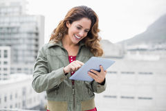 Lächelnder herrlicher Brunette auf Wintermode unter Verwendung der Tablette Stockbild