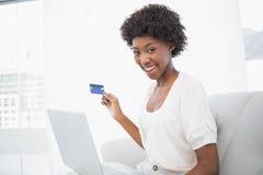Lächelnder herrlicher Brunette, der ihre Kreditkarte verwendet, um online zu kaufen stockbilder