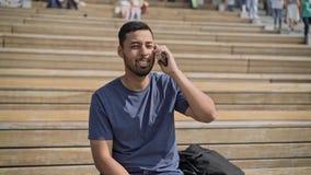 Lächelnder hispanischer Kerl, der draußen am Telefon spricht stock video