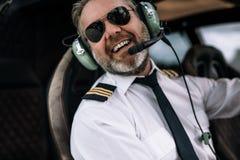 Lächelnder Hubschrauberpilot mit Kopfhörer stockfotografie