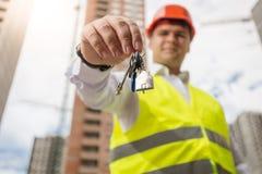 Lächelnder Ingenieur, der Schlüssel vom neuen Haus zeigt Stockfoto