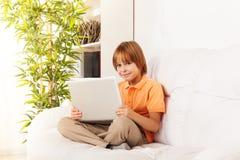 Lächelnder intelligenter Junge mit Laptop Stockfoto