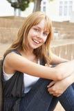 Lächelnder Jugendkursteilnehmer, der draußen sitzt Stockbild