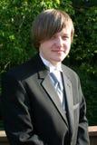 Lächelnder jugendlich Junge in der schwarzen Smokings-Vertikale Lizenzfreies Stockfoto