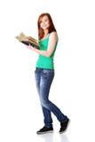 Lächelnder jugendlich Kursteilnehmer, der ein Buch anhält. Lizenzfreie Stockfotografie