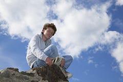 Lächelnder Jugendlicher, der auf einer Wand sitzt Stockbilder